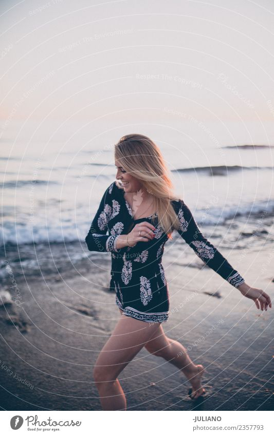 Young woman at the beach running at the ocean laughing Sun Beach Blonde Cool (slang) Dusk Joy Good Goodness Laughter Lifestyle Ocean Retro Sand Smiling Summer