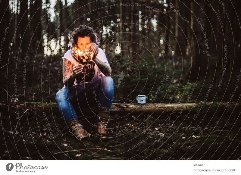 Woman with burning sparkler on a tree trunk in the forest. An enamel cup stands next to her. Cup Lifestyle Harmonious Well-being Senses Relaxation Calm