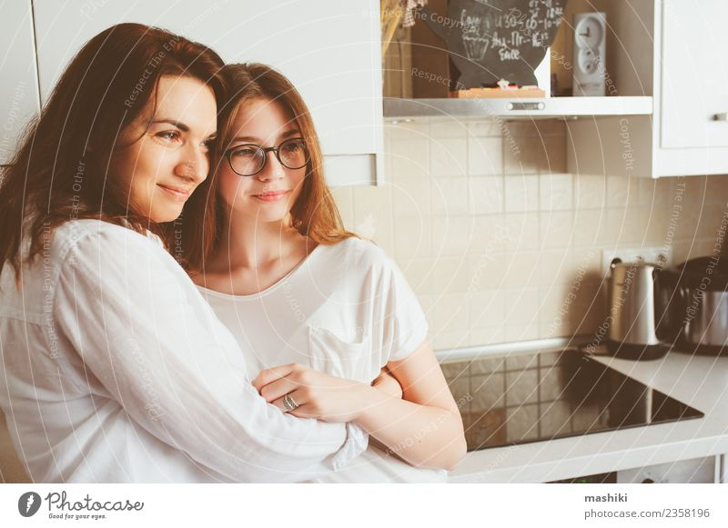 mother having breakfast with teen daughter Breakfast Lifestyle Joy Kitchen Child Mother Adults Sister Family & Relations Youth (Young adults) Smiling Embrace