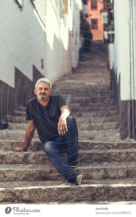 Portrait of a mature man sitting on steps in the street Lifestyle Happy Human being Masculine Man Adults Male senior Senior citizen 1 45 - 60 years Street