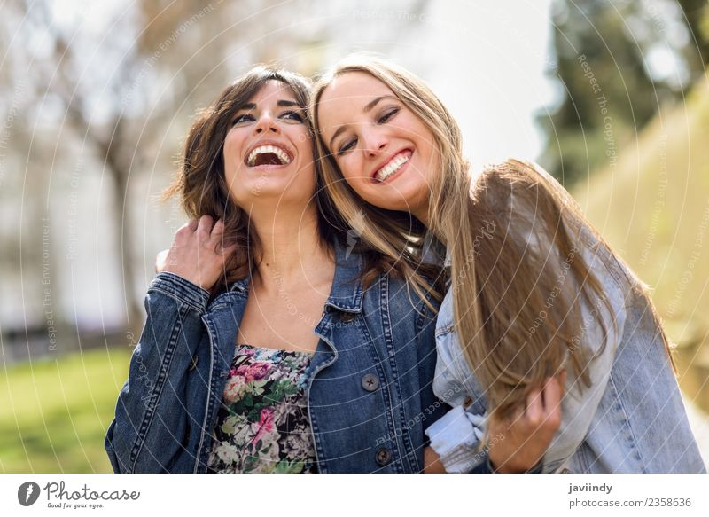 Two happy young women friends hugging in the street. Lifestyle Joy Human being Feminine Young woman Youth (Young adults) Woman Adults Friendship 2 18 - 30 years