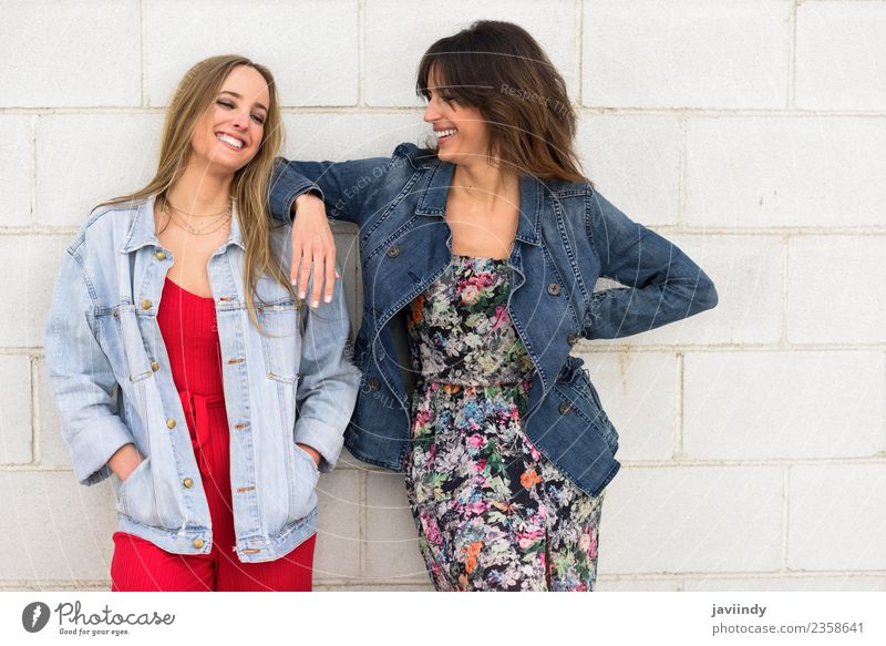 7825eeef48 Two young women smiling in urban background. - a Royalty Free Stock Photo  from Photocase