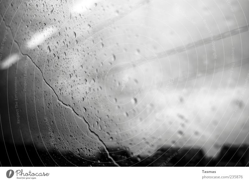 Rainy Mood Weather Bad weather Storm Cold Slice Glass Window pane Train window Drops of water Train travel Black & white photo Close-up Abstract Deserted Shadow