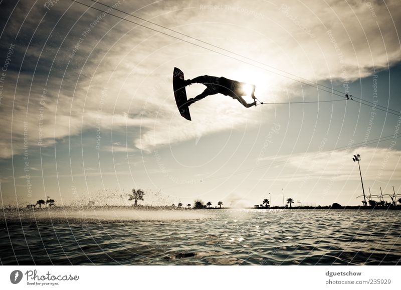 flying high Joy Leisure and hobbies Summer Sports Aquatics Masculine Man Adults Air Water Clouds Sunlight Flying Subdued colour Exterior shot Day Light Contrast
