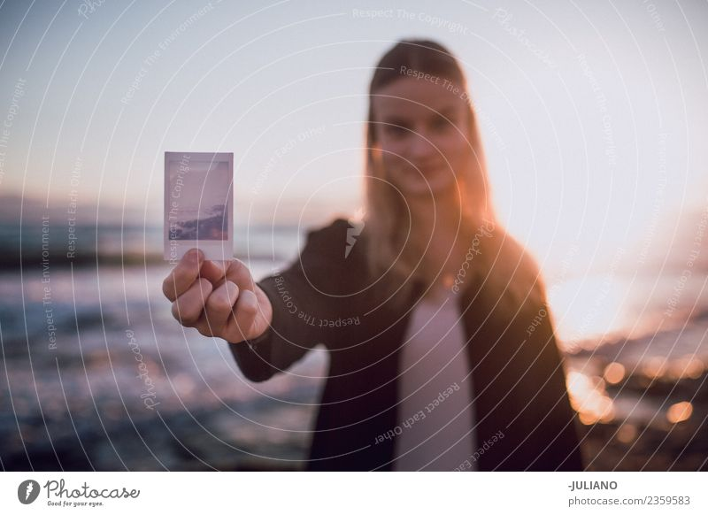 Young woman holding polaroid picture at the beach Beach Dusk Emotions Girl Happy Life Lifestyle Spain Summer Sun Sunset Warmth Adventure Communicate Freedom Joy