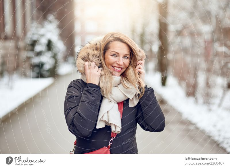 Friendly young blond woman outdoors in winter Lifestyle Happy Beautiful Face Winter Snow Woman Adults 1 Human being 45 - 60 years Park Street Fashion Coat