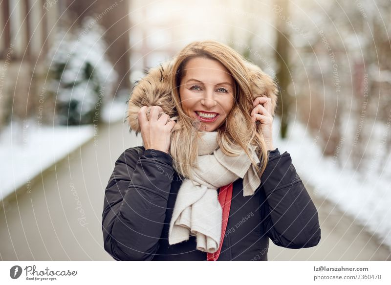 Friendly young blond woman outdoors in winter Lifestyle Happy Beautiful Face Winter Snow Woman Adults Park Fashion Coat Fur coat Scarf Blonde Smiling Happiness