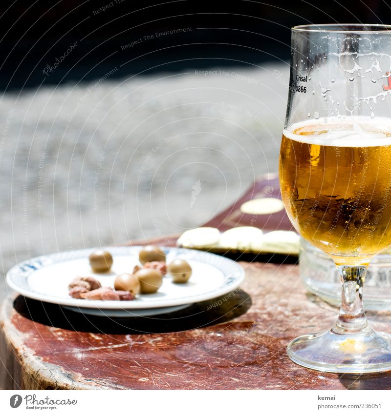 holiday lunch Food Olive Nutrition Beverage Cold drink Alcoholic drinks Beer Plate Glass Beer glass beer tulip Table Wood Lie Green olive stone Colour photo