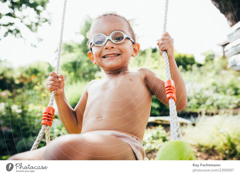 Cute black boy having fun on a swing in his parents garden Lifestyle Joy Summer Human being Toddler Boy (child) Family & Relations Infancy 1 1 - 3 years