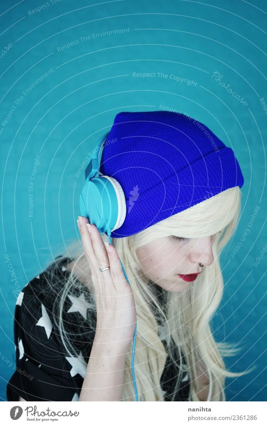 Young blond woman listening to music against a blue background Lifestyle Style Design Hair and hairstyles Leisure and hobbies Headset Technology