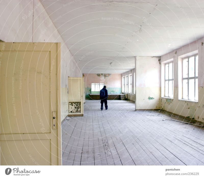 Rear view of a man standing in a large, dilapidated, old building flat. Wooden floorboards. Lost place Masculine 1 Human being House (Residential Structure)