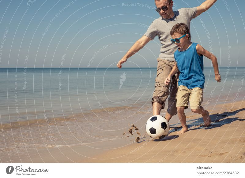 Father and son playing football on the beach at the day time. Child Human being Nature Vacation & Travel Man Summer Relaxation Joy Beach Adults Life Lifestyle