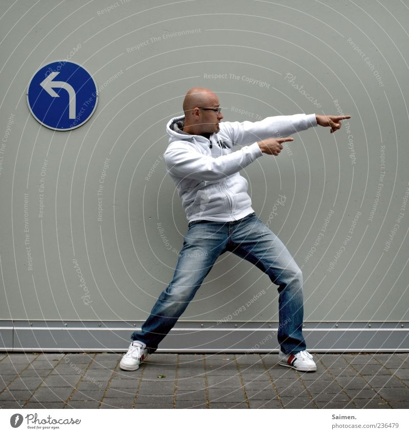 Human being Man Youth (Young adults) Adults Wall (building) Wall (barrier) Facade Masculine Stand 18 - 30 years Jeans Arrow Direction Indicate Bald or shaved head Sneakers