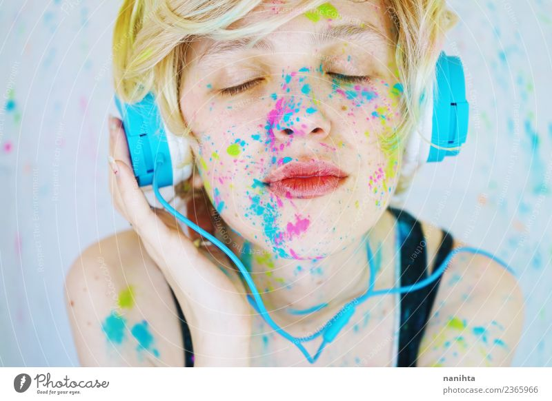 Young woman is listening to music with paint in her face Lifestyle Style Beautiful Wellness Leisure and hobbies Headset Technology Entertainment electronics