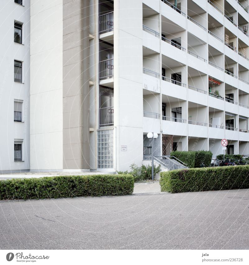 living space Plant Bushes House (Residential Structure) High-rise Manmade structures Building Architecture Facade Balcony Window Door Gloomy Town Colour photo