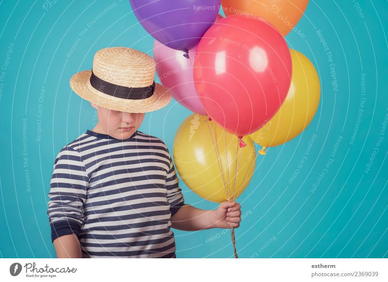 thoughtful boy with balloons on blue backgroun Child Human being Loneliness Lifestyle Think Moody Masculine Infancy Fitness Balloon 8 - 13 years Anger Hat