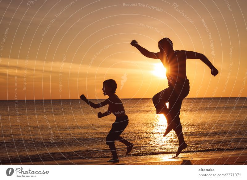 Father and son playing on the beach at the sunset time. Lifestyle Joy Happy Leisure and hobbies Vacation & Travel Trip Adventure Freedom Camping Summer Sun