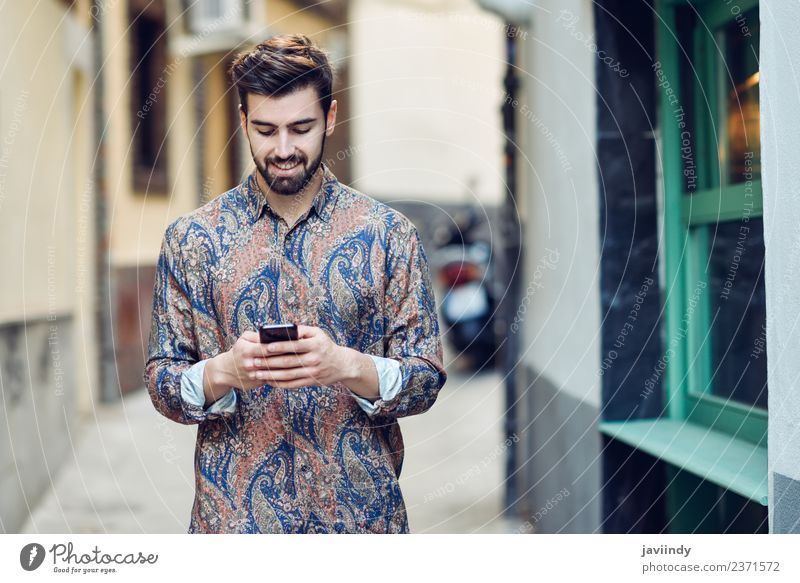 Young smiling man looking at his smart phone outdoors Lifestyle Style Beautiful Hair and hairstyles Telephone PDA Human being Young man Youth (Young adults) Man