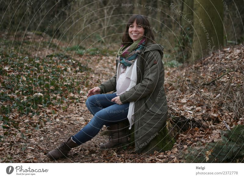 young pregnant woman with long hair sits smiling on a tree trunk in the forest Human being Feminine Young woman Youth (Young adults) Adults 1 30 - 45 years
