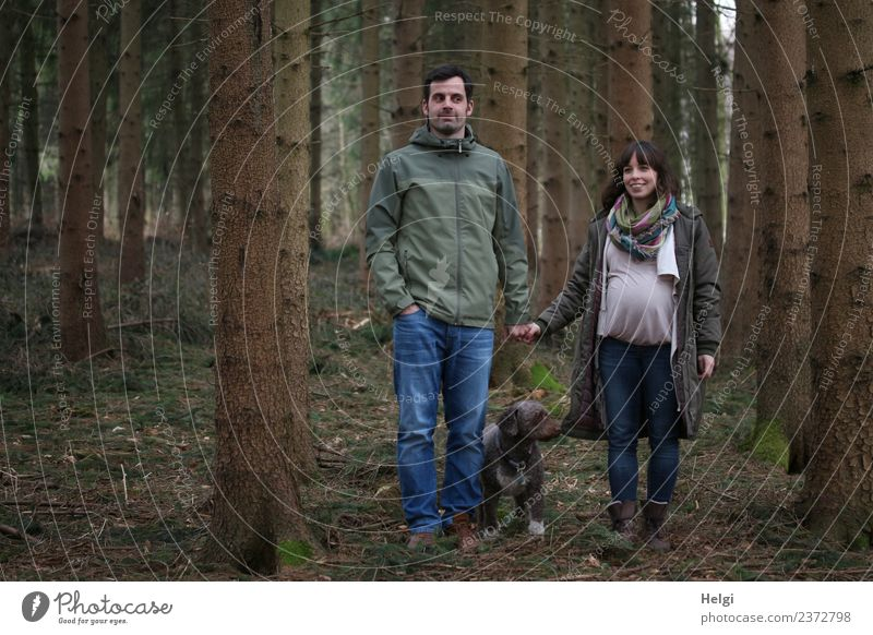 young couple with dog is in the woods, the woman is pregnant Human being Masculine Feminine Woman Adults Man Couple Partner 2 30 - 45 years Environment Nature