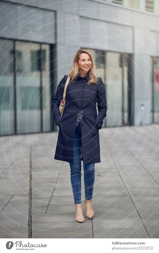 Attractive woman in jeans and an overcoat Style Happy Beautiful Work and employment Office Business Career Woman Adults 1 Human being 45 - 60 years Building