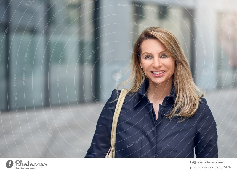 Pretty blond woman walking in an urban street Lifestyle Happy Beautiful Face Success Office Business Woman Adults 1 Human being 45 - 60 years Blonde Smiling