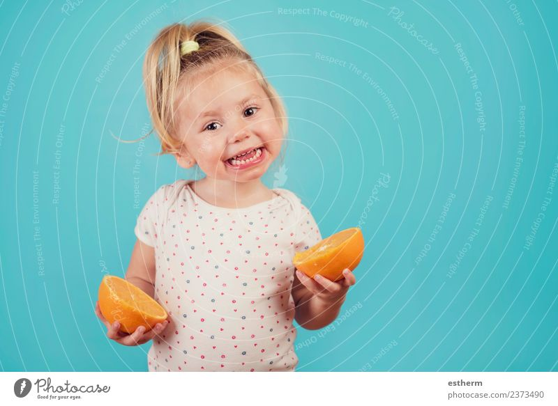 smiling baby with an orange on blue background Child Human being Joy Girl Eating Life Lifestyle Healthy Funny Feminine Laughter Food Fruit Nutrition Orange