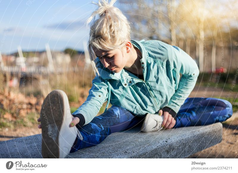 blonde woman sitting in the grass and stretching in a park Woman Human being Nature Youth (Young adults) Young woman Beautiful Tree Adults Lifestyle Natural