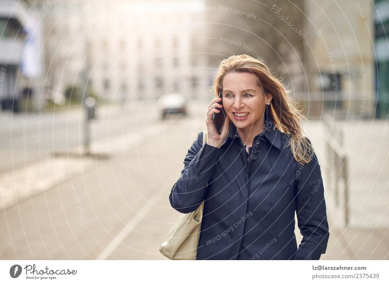 Attractive blond woman chatting on her smartphone Happy Face Business To talk Telephone Cellphone PDA Technology Woman Adults 1 Human being 45 - 60 years Street