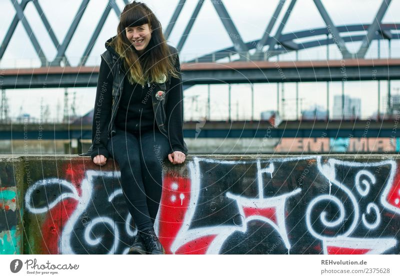 Young woman sitting on a wall Looking into the camera Full-length portrait Shallow depth of field blurriness Day Exterior shot Colour photo Rebellious naturally
