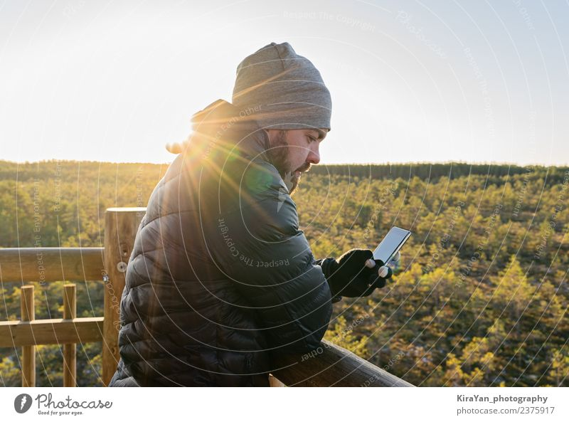 Bearded man looking at smartphone against forest Nature Vacation & Travel Man Landscape Hand Adults Lifestyle Autumn Tourism Leisure and hobbies Technology