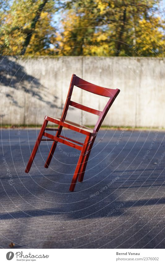 Red wooden chair in inclined position on sunny asphalt Wood Bright Chair Multicoloured Tilt Balance Insecure four-legged four-legged friends Classic Concrete