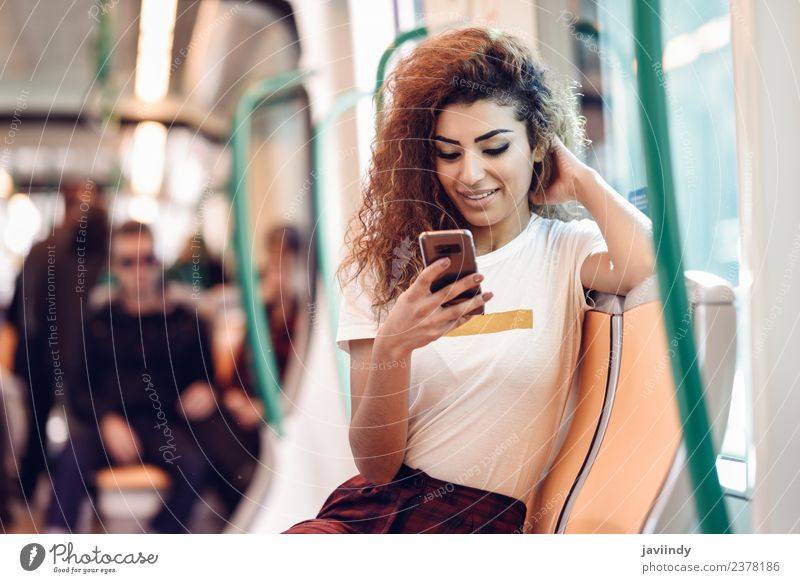 Woman inside subway train looking at her smart phone. Lifestyle Happy Beautiful Hair and hairstyles Vacation & Travel Tourism Trip Telephone PDA Human being
