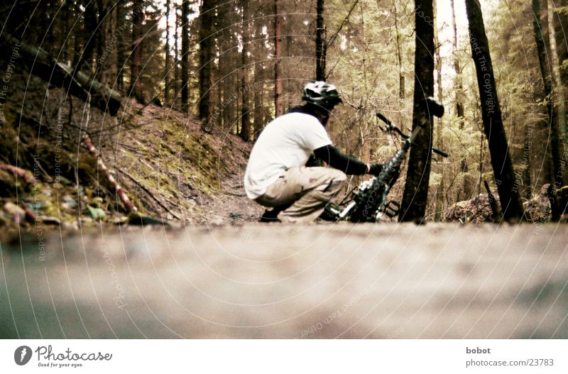 A biker squats quietly and mutely in the forest ... Mountain bike Bicycle Forest Leaf Wood Tree bark Perspire Endurance Suspension Crouch Helmet Transport