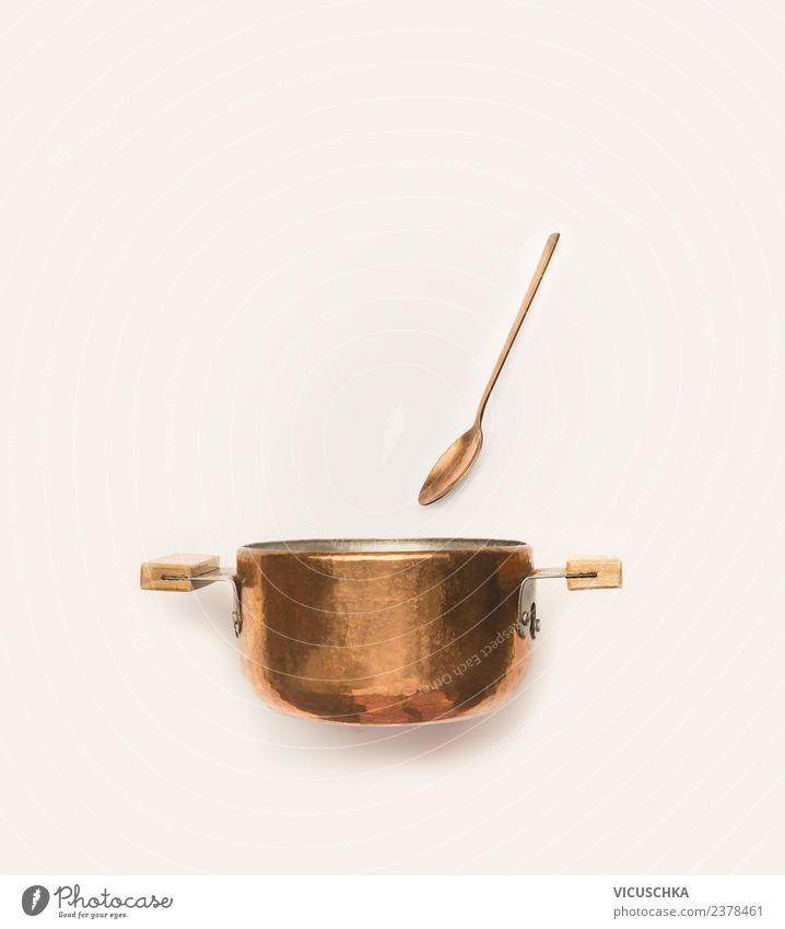 Copper pot with spoon on white background. Crockery Pot Spoon Style Design Restaurant Wooden spoon Bright background Things Colour photo Interior shot