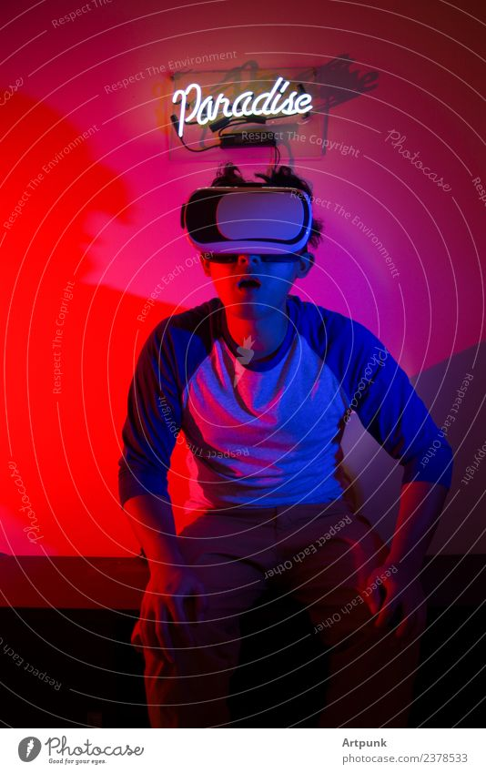 A young man enjoying a VR experience Blue Red Technology Computer Signage Illustration Paradise Neon light Visual spectacle Experience Virtual Gel Headset