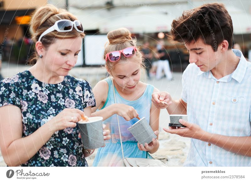 Family spending time together in the city centre enjoy eating ice cream on a summer day. Mother, teenage girl and boy spending quality time on sunny afternoon eating sweet dessert. Downtown area, old town in the background