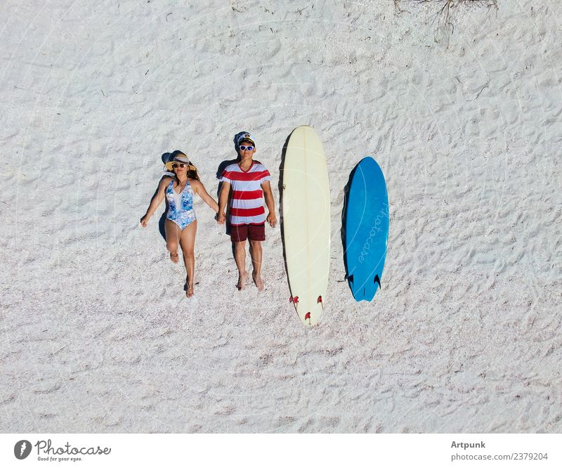 Aerial view of a surfing couple laying on the beach