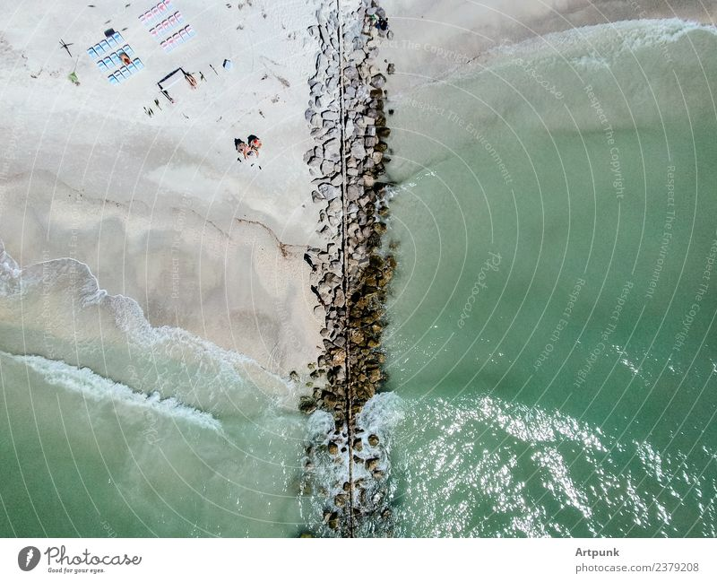 Aerial view of a jetty Jetty Water Waves Ocean Aircraft Vantage point Drone Summer Beach Chair Human being Green Sand Sun Rock Stone block Bikini