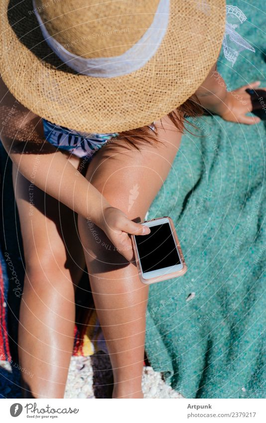 A young woman texting on the beach Beach Youth (Young adults) 18 - 30 years Young woman Woman Legs Hat Blanket Towel PDA Technology Exterior shot wifi Data