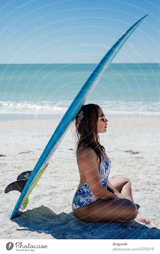 A young woman sitting under a surfboard 18 - 30 years Woman Latin American South America Asians Summer Surfboard Beach Sand Sun Ocean Water Bikini Long-haired