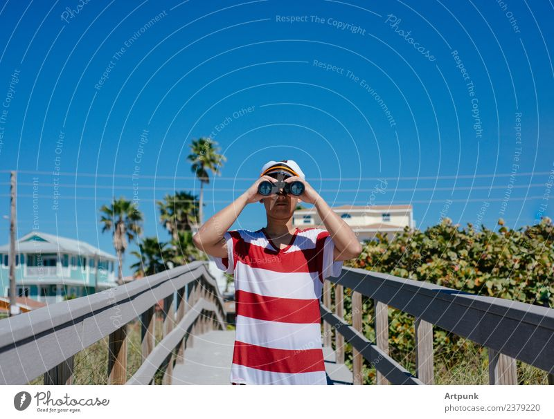 A young sailor looking through a pair of binoculars Binoculars Sailor Summer Beach Vacation & Travel Hat Captain Palm tree Tropical Jetty Plant Sand Tree Sky