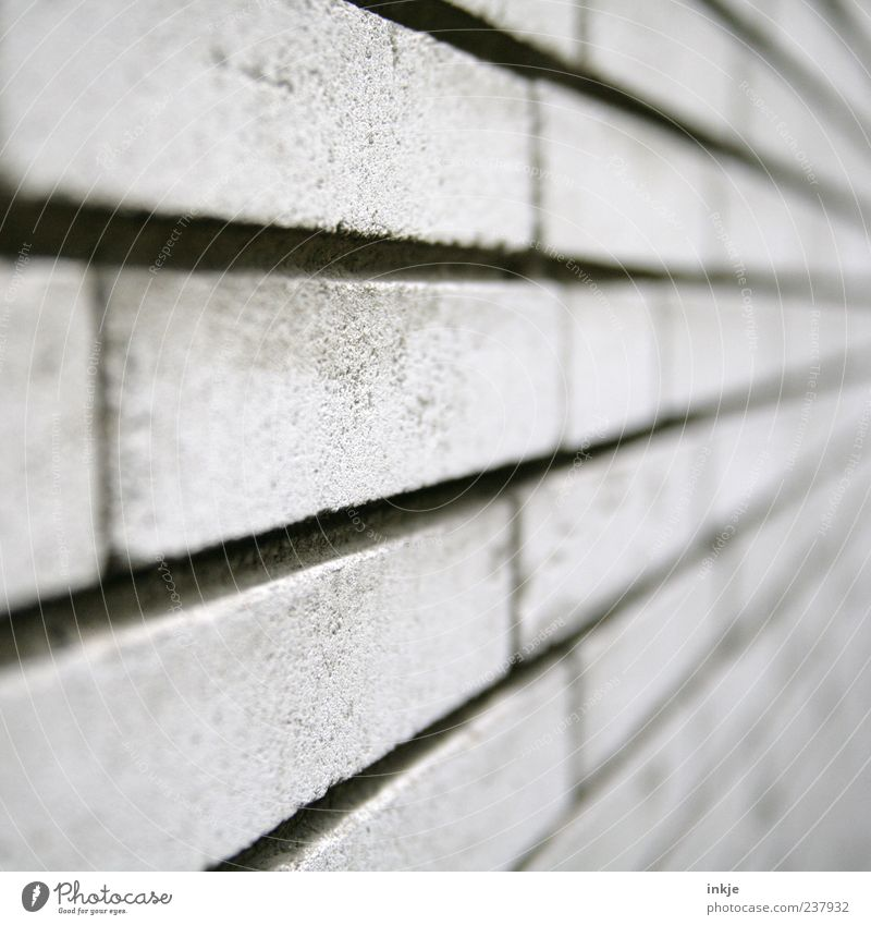always on the wall long Wall (barrier) Wall (building) Facade Sandstone Stone wall Concrete Brick Line Stripe Cold Gray Vanishing point Brick wall Colour photo