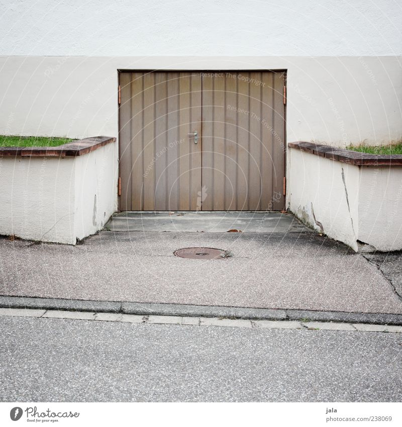 garage Grass Meadow Wall (barrier) Wall (building) Facade Garage Garage door Highway ramp (entrance) Street Sidewalk Gloomy Brown Gray Green Asphalt