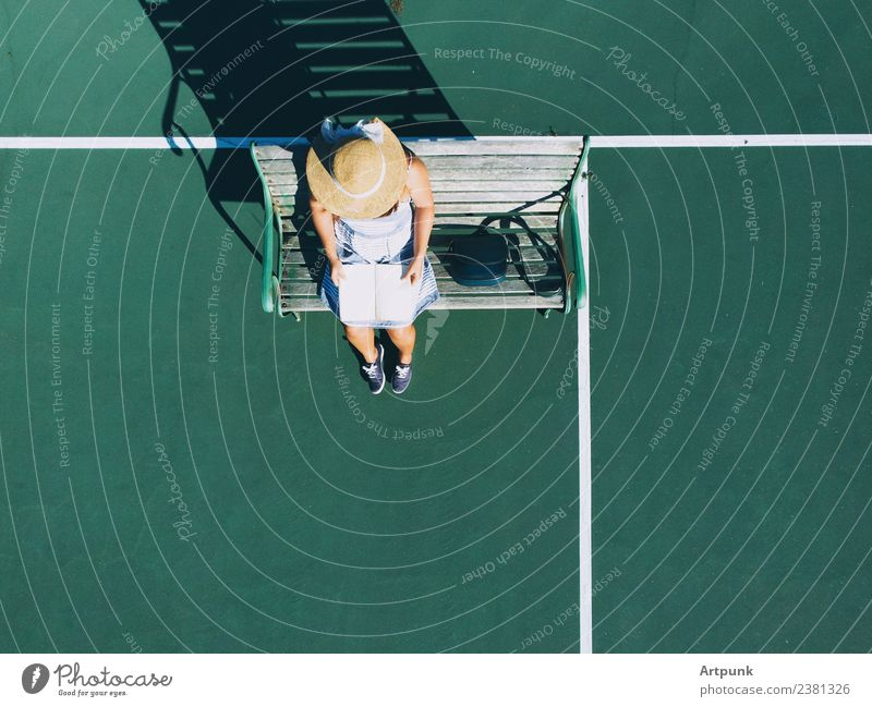 An aerial view of young woman reading a book Book Aircraft Bag Reading Reader Hat Bench Shadow Drone Tennis court Exterior shot Sunset Summer Sunbeam