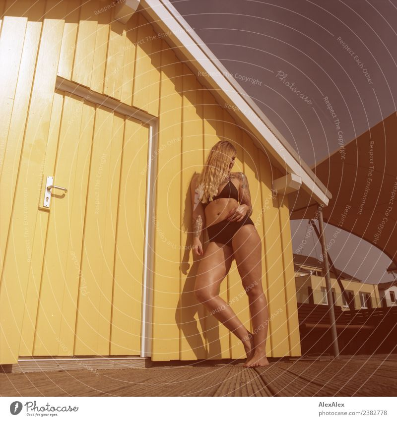Woman with long hair leaning on yellow wooden house in summer Lifestyle Style Joy Beautiful Body Wellness Well-being Summer Summer vacation Sunbathing
