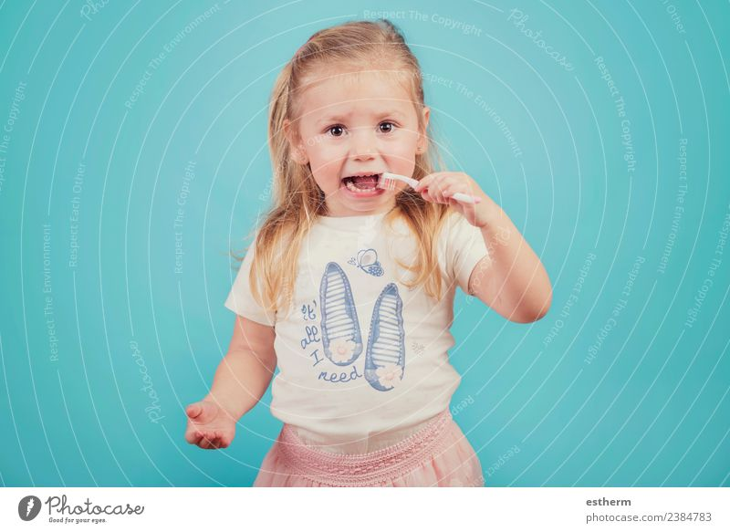 little girl with toothbrush on blue background Lifestyle Joy Personal hygiene Health care Human being Feminine Baby Girl Infancy 1 3 - 8 years Child Toothbrush