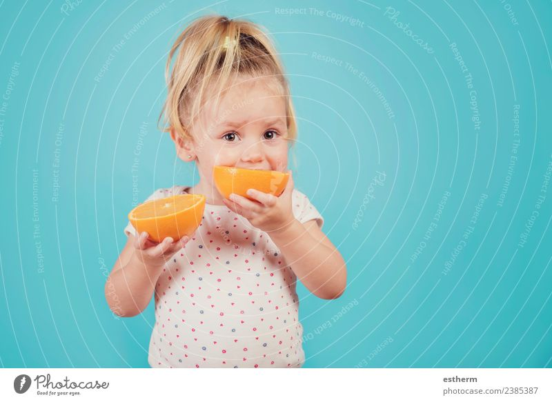 baby eating an orange on blue background Food Fruit Orange Nutrition Eating Lunch Lifestyle Joy Healthy Eating Human being Feminine Baby Girl Infancy 1