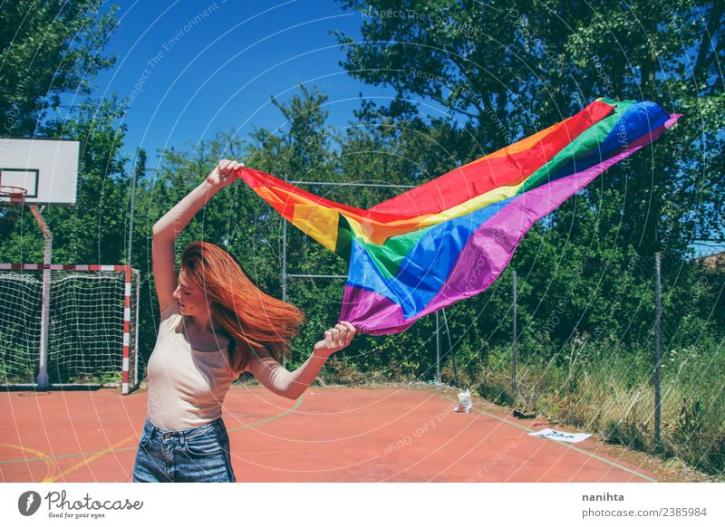 Young woman waving a rainbow flag Lifestyle Style Design Schoolyard Student Human being Feminine Homosexual Young man Youth (Young adults) 1 18 - 30 years