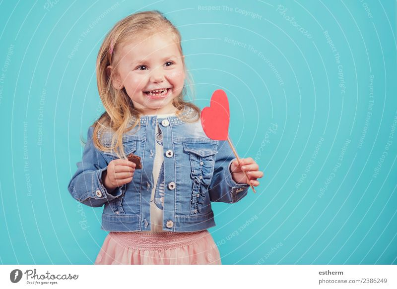 smiling baby with a heart on blue background Child Human being Joy Girl Lifestyle Love Funny Emotions Feminine Laughter Feasts & Celebrations Infancy Smiling